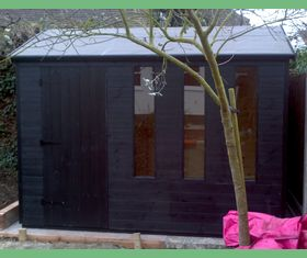 10 x 8 apex plank taller with three slit windows painted black